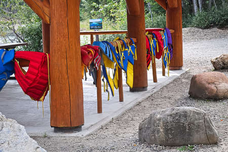 A row of lifejackets hanging on a rail Stock Photo