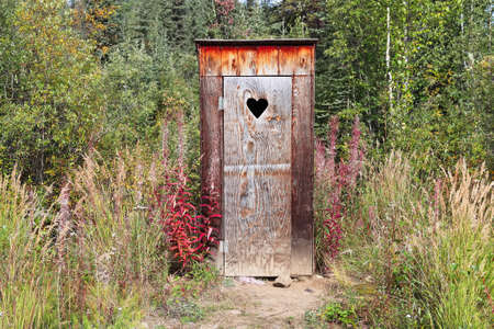An outhouse in a wooded area with a heart window