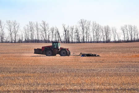 A tractor plows the field in the distance. Banco de Imagens