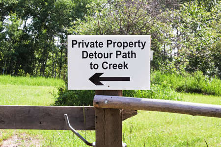 A private property detour path to creek sign Stock Photo