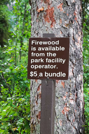 A vertical firewood is available from park facility sign.