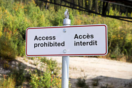 An access prohibited sign in english and french.