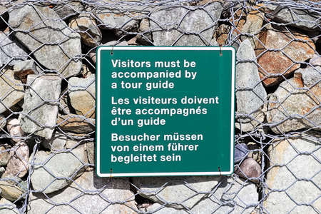 A vistors must be accompanied by a tour guide sign