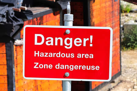 A red danger hazardous area sign in english and french