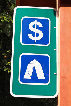 A ten and money sign at a campground.