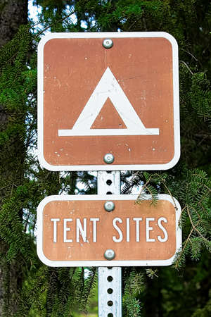 A brown campground test sites sign on a pole