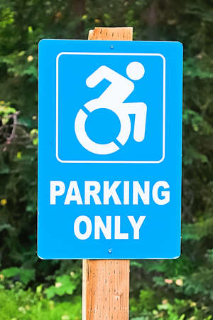 A blue handicap parking only sign on a post