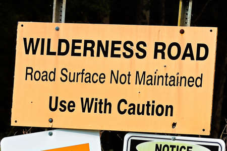 An orange wilderness road, use with caution sign