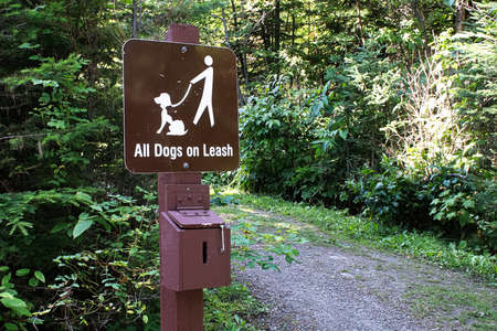 An all dog on leash sign with payment box