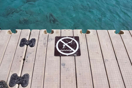 A no diving sign on the edge of a dock