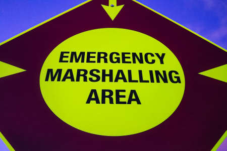 A neon emergency marshalling area sign with arrows