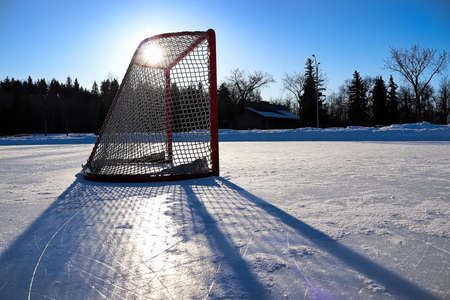 Sun silhouetting a empty hockey net on a frozen pond Stock Photo