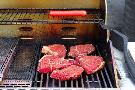 Raw seasoned steaks on a BBQ grill