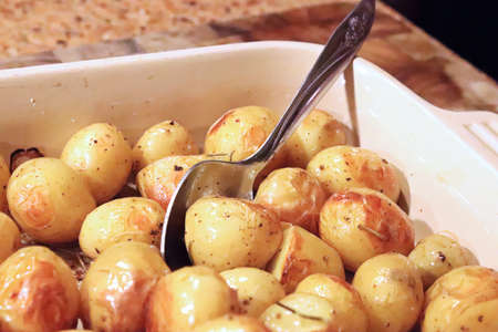 Roasted baby potatoes out of the oven with a spoon.
