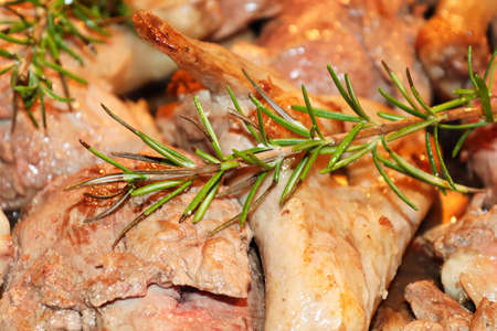 Closeup of rosemary over cut up duck pieces