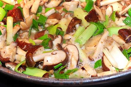 Closeup of mushrooms and leeks cooking in a pan