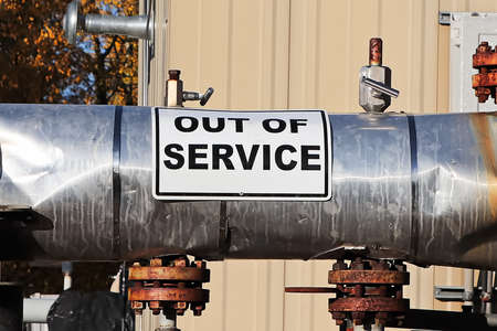 An Out of Service sign on an oil pipeline