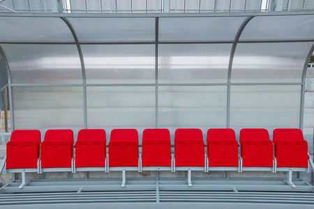 Red reserve and staff coach bench in sport stadium Stock Photo