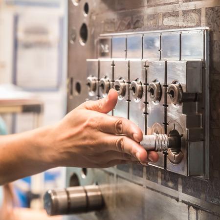 Inserción Trabajador piezas de repuesto en la máquina de moldeo por inyección Foto de archivo
