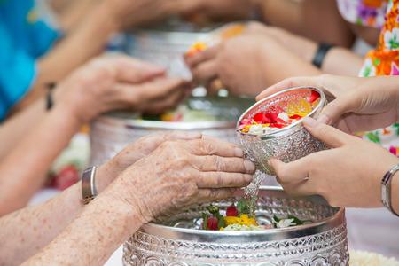 尊敬される年長者とソンクランの日に祝福を与えるの手に水を注ぐ 写真素材