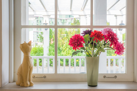 Vase  with a flower and cat doll on the windowsill country house photo