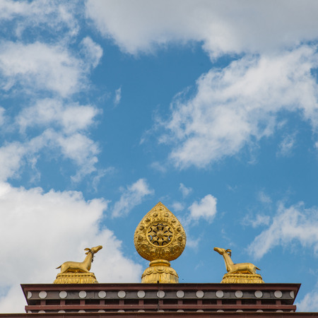 dharma: The sculpture of the wheel of Dharma and two deer on the roof Stock Photo