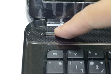 shut down: a finger is pushing the power button to wake laptop up Stock Photo