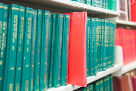 thesis: Book in a bookshelf standing out at university library Editorial