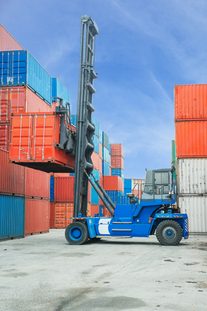 dockside: Crane lifter handling container box loading to truck in import export zone