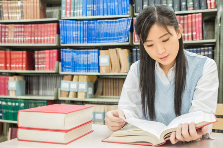 Asian student reading book in library at university photo