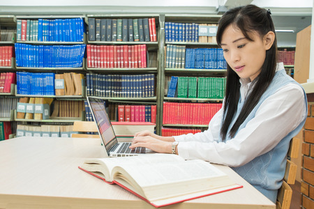 Asian student using laptop computer in university library photo