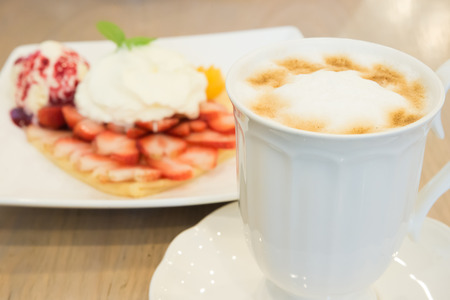 Cappuccino coffee cup and vanilla  ice cream with strawberry and whipp cream in background photo