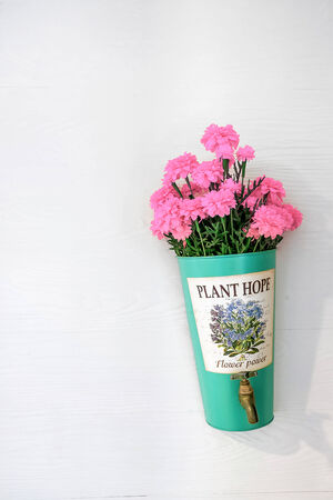 implanted: flower pot with pink flowers hanging on a house wall