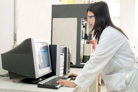 Scientist works at computer scientific analysing data out scientific test in chemistry laboratory photo