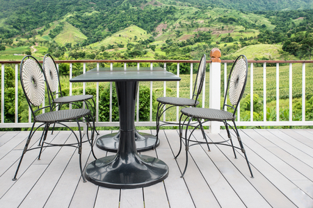 Table and chair on terrace with nature in background photo