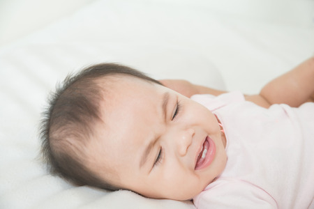 Asian cute girl baby lying in bed photo