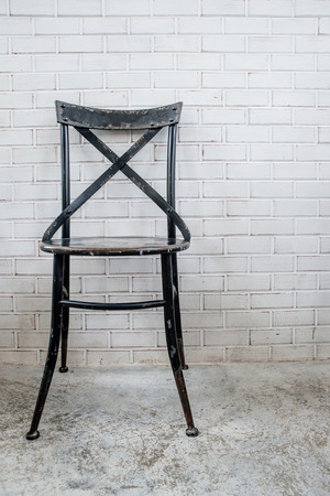 Classic iron chair with white brick wall photo