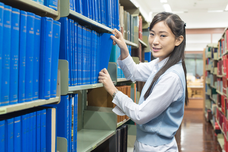Young asain student picking a book from the bookshelf Stock Photo