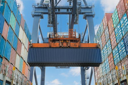 cargo container: Shore crane lifts container during cargo operation in port