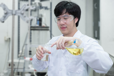 analytical chemistry: Scientist filling an Erlenmeyer flask in a chemical laboratory