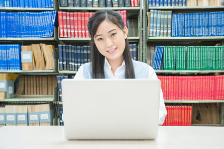 Asian pretty female student using laptop in library photo