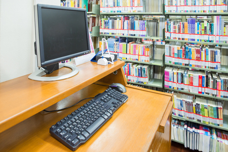 computer in a library with many books and shelves in the background photo