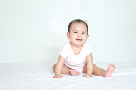 Asian cute girl baby is smiling in bedroom Stock Photo