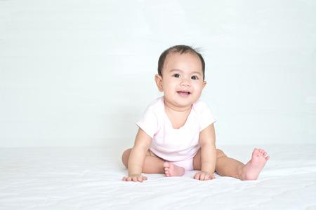 Asian cute girl baby is smiling in bedroom Foto de archivo