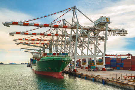 dockyard: Container Ship in terminal working with shore crane at dock Editorial