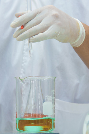 titration: Researcher doing the experiment, titration of the reagent in the flask Stock Photo