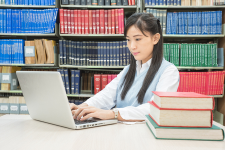 Asian female student typing on notebook in library photo