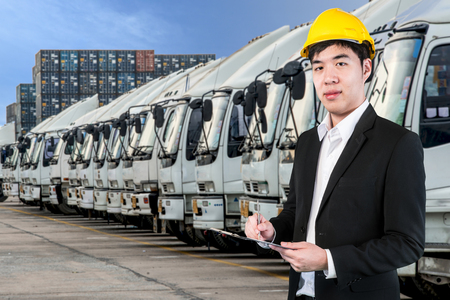 Transportation engineer with trucks of a transporting company in a row photo