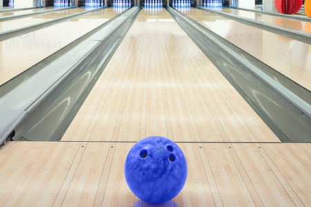 Balls on bowling alley against ten pins photo