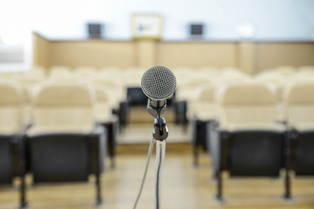 public speaking: before a conference, the microphones in front of empty chairs. Stock Photo
